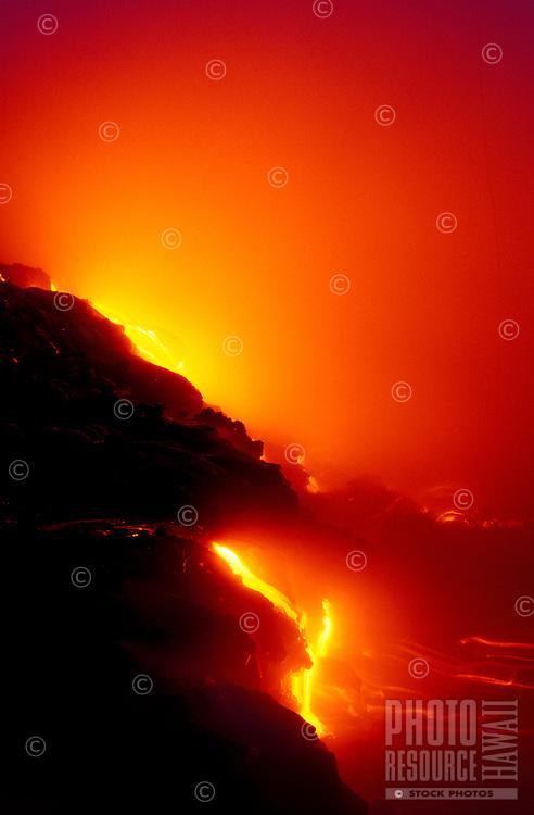 Vivid fiery streams of lava flow from cliffs into the ocean.