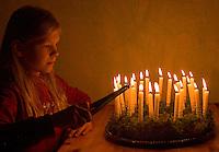 Kinder basteln einen Lichterkranz für die Adventszeit, Adventskranz, Kind zündet die Kerzen auf dem fertigen Lichterkranz an, Lichterkranz mit 24 brennenden Kerzen für den 1. bis 24. Dezember