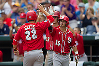 North Carolina State outfielder Bryan Adametz (15) greets teammate third baseman Grant Clyde (22) at the plate during Game 3 of the 2013 Men's College World Series between the North Carolina State Wolfpack and North Carolina Tar Heels at TD Ameritrade Park on June 16, 2013 in Omaha, Nebraska. The Wolfpack defeated the Tar Heels 8-1. (Andrew Woolley/Four Seam Images)