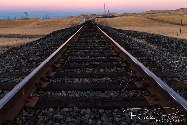 Union Pacific rails in the California hills at dusk west of Tracy, California