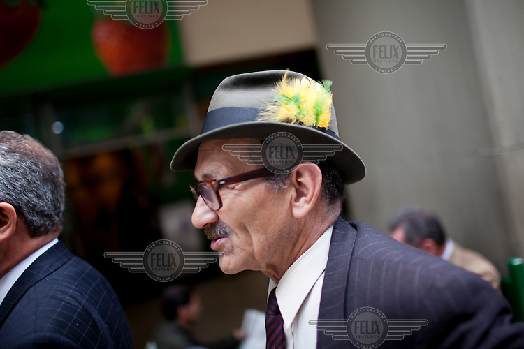 A man wears a hat with feathers.