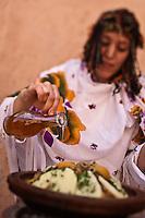 Afrique/Afrique du Nord/Maroc/Province d'Agadir/Tighanimine Elbaz: Ecolodge Atlas Kasbah -  Préparation sur le brasero du  tajine de poulet aux  pommes de terre et oignons, ajout de l'Huile d'Argan