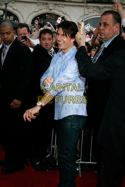 "TOM CRUISE.""Knight And Day"" German Film  Premiere, Munich, Germany, .July 21st, 2010.half 3/4 length blue shirt wet soaked side  arm wrist watch jeans security assistant umbrella .CAP/PE.©Peter Eden/Capital Pictures."