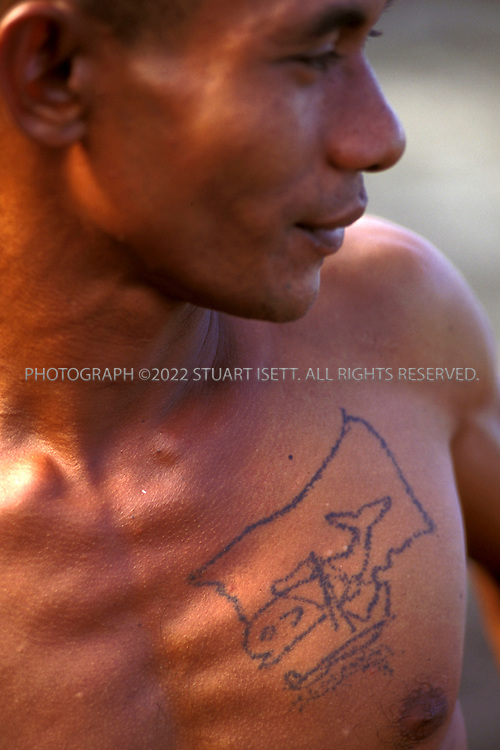 Lamalera, Indonesia..A whaler with a tattoo that shows a sperm whale being hunted stands on the beach at Lamalera...Photograph by Stuart Isett.©2003 Stuart Isett