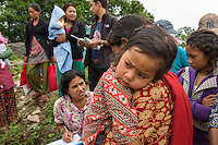 Nepal, Dholakha, Charikot earthquake relief work. The NGO Loom, unpacking supplies in the hard hit Dolakha region near the second epicenter. They have a $5000 TEWA funded grant (through Global Fund for Women) and are using it to hand out mosquito nets, buckets and dignity kits for women with newborn children. These kits include tootpaste, lentils, rice, baby massage oil, baby clothes, baby food, sanitary pads, a shawl. Bishnu Adlikan from Loom handing out to new mothers and babies during distribution.
