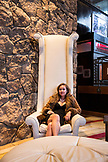 USA, Colorado, Aspen, woman sits in a tall backed chair in the lobby of the Sky Hotel