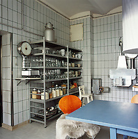 Industrial shelving occupies one corner of the kitchen/dining area and is filled with glassware, plates and storage jars