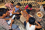 Cambodian boys study English words and work cutting out leather art