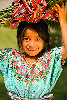 Portrait of young girl carrying load on her head with the colorful print patterned clothes of women in the famous market day color of the Highlands in village of Solola Guatemal