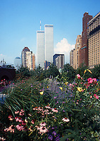 The twin towers of the World Trade Center rise above a flower bed in New York City.  (Photo by Brian Cleary/www.bcpix.com)