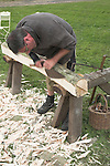 Man demonstrating traditional woodcraft using an axe to shape a log