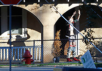 The suspect walked outside his home with his arms up and pants around his knees moments before police arrested him without incident Sunday outside of 2500 Jefferson Park Avenue in Charlottesville, Va. The multi-hour stand off ended when police shot tear gas into the home forcing the suspect to walk out and surrender. (Photo/The Daily Progress/Andrew Shurtleff)