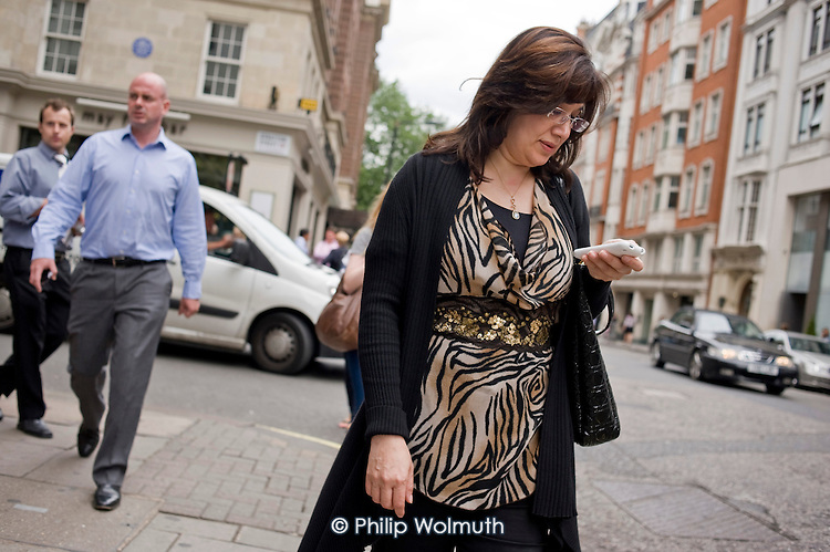 Woman using a mobile phone, Mayfair, London.
