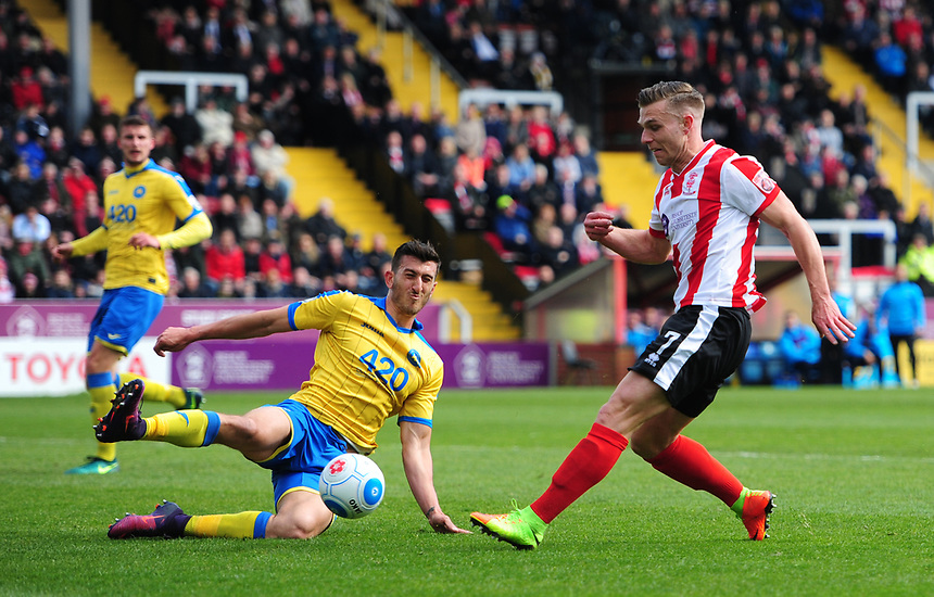Lincoln City's Jack Muldoon has a shot blocked by Torquay United's Giancarlo Gallifuoco<br /> <br /> Photographer Chris Vaughan/CameraSport<br /> <br /> Vanarama National League - Lincoln City v Torquay United - Friday 14th April 2016  - Sincil Bank - Lincoln<br /> <br /> World Copyright &copy; 2017 CameraSport. All rights reserved. 43 Linden Ave. Countesthorpe. Leicester. England. LE8 5PG - Tel: +44 (0) 116 277 4147 - admin@camerasport.com - www.camerasport.com