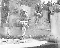 Sgt. Norwood Dorman, Benson, N.C., stops to rest at the memorial to the Italian soldier of World War I, Brolo, Sicily.  August 14, 1943.  Lt. Robert J. Longini. (Army)<br /> NARA FILE #:  111-SC-179879<br /> WAR & CONFLICT BOOK #:  1026