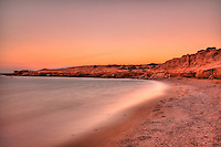 Sunset at a wild beauty beach with eaten by the sea cliffs and unique caves in Karpathos, Greece