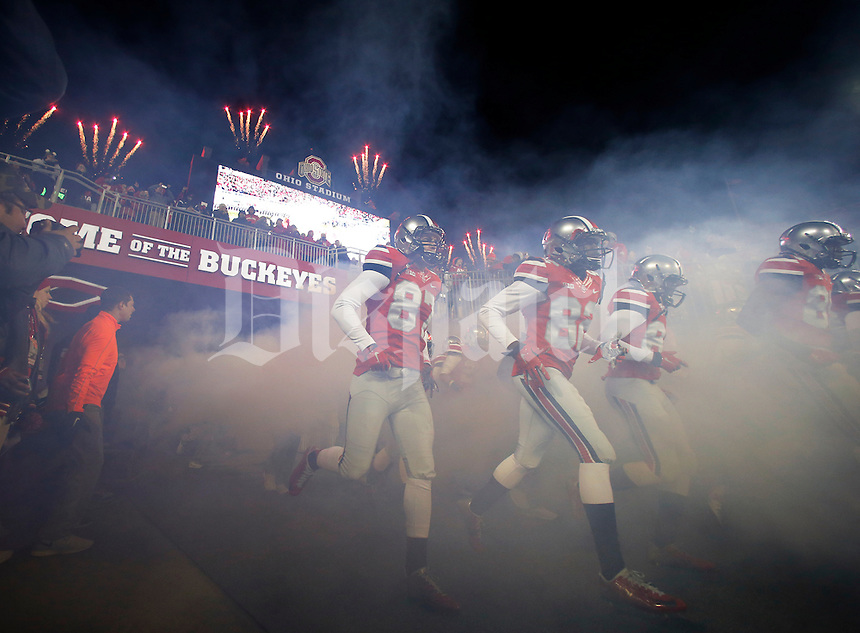 With pyrotechnics in the background, Ohio State players take the field prior to the first quarter of the NCAA football game against the Illinois Fighting Illini at Ohio Stadium on Nov. 1, 2014. (Adam Cairns / The Columbus Dispatch)