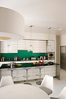 This elegant kitchen/dining area features a breakfast bar of green glass matching the splashback and a tiled floor of ground glass