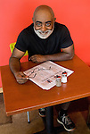 African American man sitting at cafe table, smiling