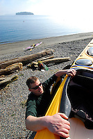 Male paddler unloading yellow kayak from roof rack, for a day of paddling in the San Juan Islands, Sea Kayaking the San Juan Islands, WA.