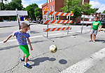 Nicholas Krawat, 7 (left) and Ale Poggioli, 9, both of St. Louis, kick a soccer ball back and forth during halftime of the World Cup game. Their parents had taken them to the Amsterdam Tavern in south St. Louis where a big screen television was set up in the street in front of the tavern for the championship game between Croatia and France on Sunday July 15, 2018.               Photo by Tim Vizer