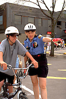 Officer with teen age 35 and 15 at community Youth Express Bicycle Safety Rodeo.  St Paul Minnesota USA