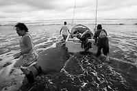 Family helping to push the boat in to the water. Jaque, Panama.