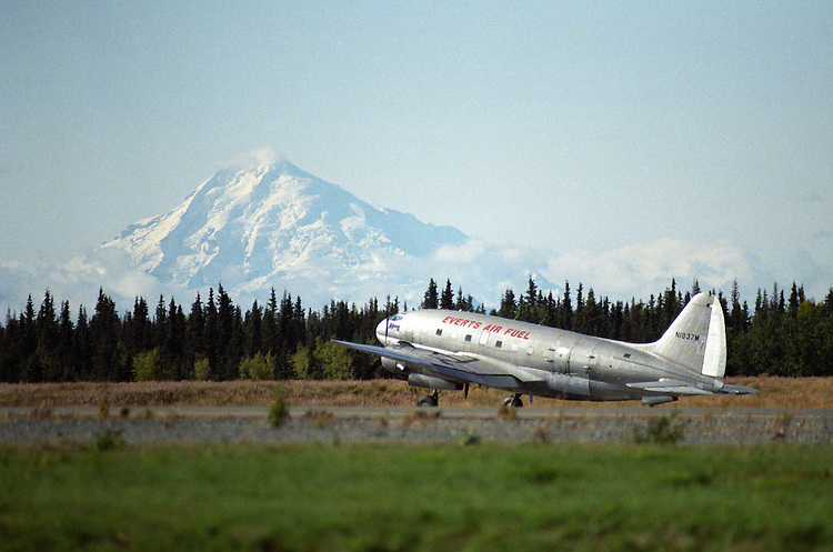 Mount Redoubt is visible from Kenai Municipal Airport, where an Everts Air Fuel Curtiss-Wright C-46F Commando fuel plane prepares for takeoff. The active volcano disrupts both local and international aviation when it erupts.