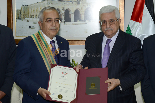 (FILES) This file photo taken on June 8, 2013 shows Palestinian President Mahmoud Abbas (Abu Mazen) honors former Prime Minister Salam Fayyad in the West Bank city of Ramallah. According to media, a sudden meeting was held between Palestinian President Mahmoud Abbas and former Palestinian Prime Minister Salam Fayyad, before days ago, in the West Bank city of Ramallah. Photo by Thaer Ganaim