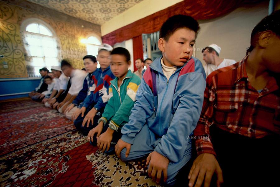 1997..Kazakhstan. Atyrau. Muslim Kazakh children pray in the only mosque that was tolerated during the Soviet era..Kazakhstan. Atyrau. Des enfants kazakhs musulmans prient dans la seule mosquée qui était tolérée pendant l'ère soviétique.