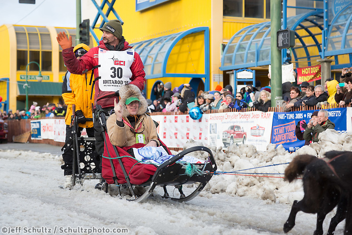 Lance Mackey and team leave the ceremonial start line with an Iditarider at 4th Avenue and D street in downtown Anchorage, Alaska during the 2015 Iditarod race. Photo by Jim Kohl/IditarodPhotos.com