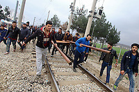 Pictured: Refugees use a ram try to bring down the barbed wire gate of the fence Monday 29 February 2016<br /> Re: A crowd of migrants has burst through a barbed-wire fence on the FYRO Macedonia-Greece border using a steel pole as a battering ram.<br /> TV footage showed migrants pushing against the fence at Idomeni, ripping away barbed wire, as FYRO Macedonian police let off tear gas to force them away.<br /> A section of fence was smashed open with the battering ram. It is not clear how many migrants got through.<br /> Many of those trying to reach northern Europe are Syrian and Iraqi refugees.<br /> About 6,500 people are stuck on the Greek side of the border, as FYRO Macedonia is letting very few in. Many have been camping in squalid conditions for a week or more, with little food or medical help.