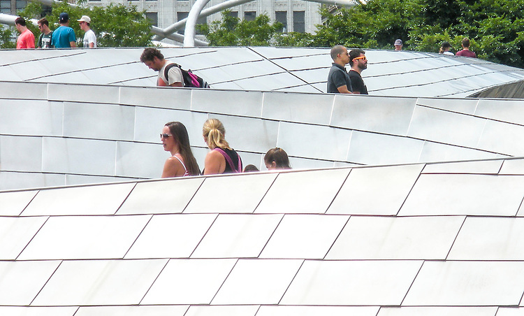 Flanked by the Jay Pritzker Pavilion, tourists make their way across the serpentine-like BP Pedestrian Bridge that connects Millennium Park to Grant Park in downtown Chicago. Designed by Pritzker prize-winning architect Frank Gehry, the stainless steel structure opened along with the rest of Millennium Park on July 16, 2004.(DePaul University/Jamie Moncrief)