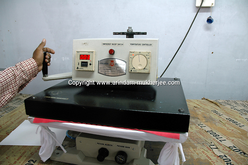 A man working with an imported compressing machine at Popy's printing factory in Tirupur, Tamilnadu. After lifting of quota system in textile export on 1st january 2005. Tirupur has become the biggest foreign currency earning town of India.