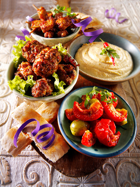 Party buffet food with Humous, meatballs, chicken satay and sundried tomatoes