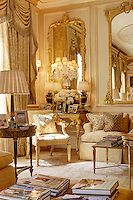 The corner of a luxurious sitting room with gilt mirrors and antique furniture. The room is furnished in neutral tones.