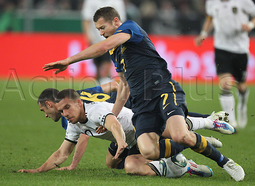 29 03 2011  Lukas Podolski 10 DFB in duel for the Ball against Bret Emerton 7 with Carl Valeri 16 Germany Australia versus German  national team DFB friendly  in Moenchengladbach
