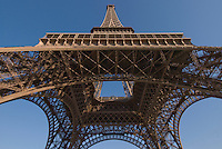 Eiffel Tower.  Early morning shot from base at Champs de Mars, looking up.  Details of the 4 arched legs and truss structure.  Clear, blue, cloudless sky.  July 2008