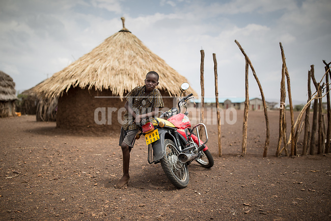 A kid leans on a motorcycle iin Kakuma refugee camp in Kenya.Kakuma refugee camp in North of Kenya. Kakuma is the site of a UNHCR refugee camp, established in 1991. The population of Kakuma town was 60,000 in 2014, having grown from around 8,000 in 1990. In 1991, the camp was established to host the 12,000 unaccompanied minors who had fled the war in Sudan and came walking from camps in Ethiopia.