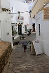 Woman walking in cobbled alleyway whitewashed buildings in Vejer de la Frontera, Cadiz Province, Spain