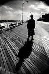 Man & shadow on boardwalk