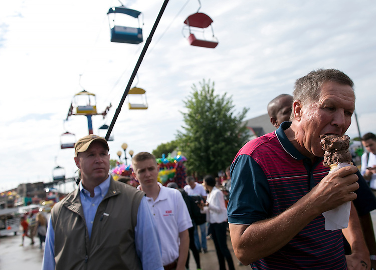 UNITED STATES - August 17: Republican presidential candidate and Ohio Governor John Kasich samples an ice cream cone given to him by a fairgoer at the Iowa State Fair on Tuesday, August 18, 2015 in Des Moines, Iowa. (Photo By Al Drago/CQ Roll Call)