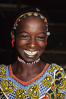 Tortiya, Ivory Coast, Cote d'Ivoire, West Africa.  Fulani Girl Smiling.  Headwear Decorated with Coins.
