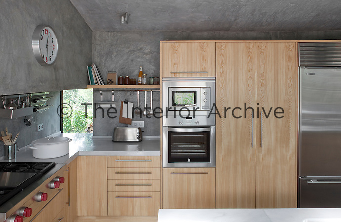 The contemporary kitchen features fitted cupboards and marble work tops