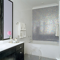 In the bathroom the starkness of a striking black and white vanity unit is offset by the iridescent mosaic tiles covering the wall and floor