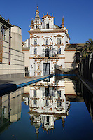 View from the front of the  Hospital de la Caridad (Charity Hospital), Seville, Spain, pictured on January 3, 2007, in the afternoon, reflecting in the pool of the Teatro de la Maestranza (left foreground) which was built in 1991 for the Seville Expo, 1992. Founded in 1674 by Miguel de Manara, the Hospital de la Caridad is a refuge for poor and elderly people. An outstanding example of Sevillian Baroque with whitewashed walls and terracotta stonework, it was designed by Pedro Sanchez Falconete. Picture by Manuel Cohen.