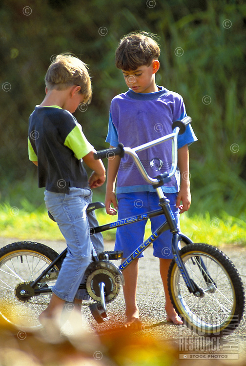 Two young boys, one sitting on a bicycle, share a moment of conversation in a green park.