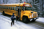 Two boys getting onto a school bus on a snowy day in Rockport, Maine, USA