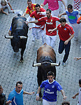 Participants run in front of Victorinano del Rio Cortes's bulls during the sixth San Fermin Festival bull run, on July 12, 2012, in Pamplona, northern Spain. The festival is a symbol of Spanish culture that attracts thousands of tourists to watch the bull runs despite heavy condemnation from animal rights groups. (c) Pedro ARMESTRE
