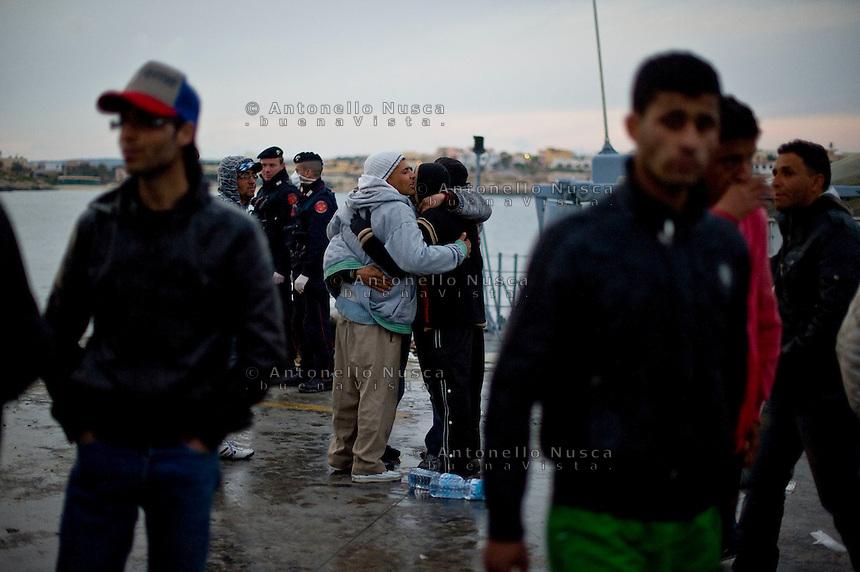 Immigrati Tunisini si abbracciano dopo essere sbarcati nel porto di Lampedusa. Immigrants embrace each other as they landed at the port of Lampedusa .